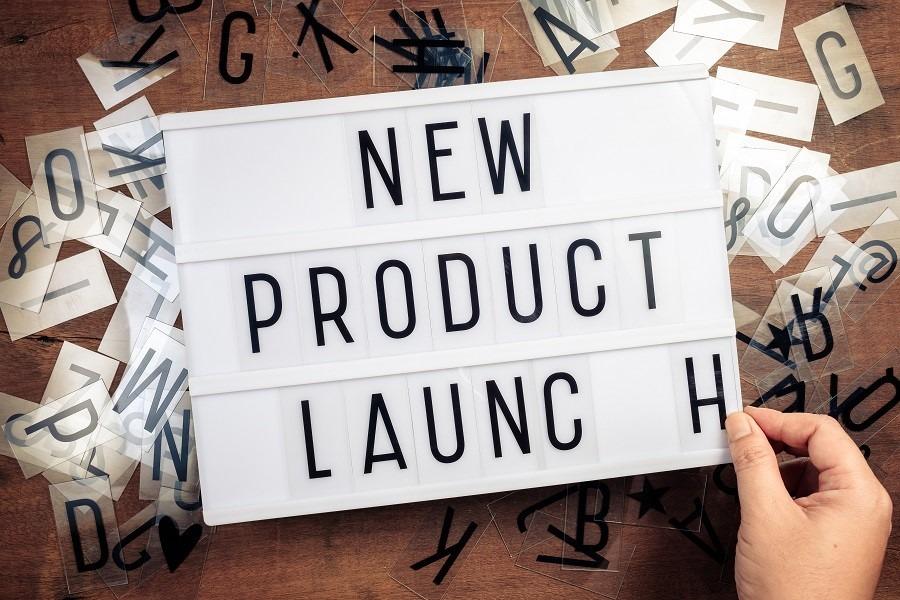 """Une main tenant une feuille sur lequel est écrit """"lancement de nouveau produit"""""""